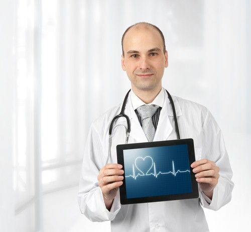 Doctor holding a tablet showing a graph and a heart